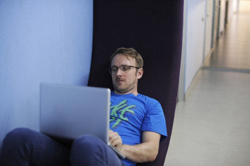 Mężczyzna w okularach trzyma na kolanach laptop