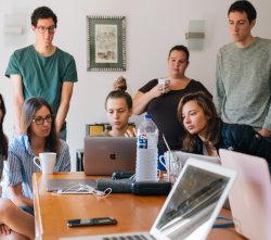 Pracownicy firmy patrzą się w ekran laptopa
